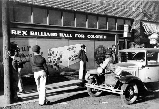 Группа афро-американцев перед входом в бильярдную с надписью Для цветных