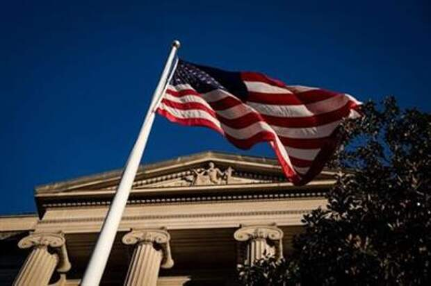 An American flag waves outside the U.S. Department of Justice Building in Washington, U.S., December 15, 2020. REUTERS/Al Drago