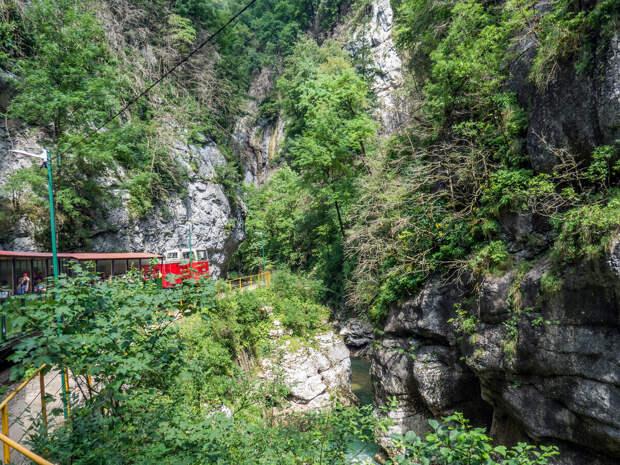под нависающими скалами, а внизу шумит река Курджипс.